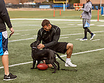 March 19, 2017. Chapel Hill, North Carolina.<br /> <br /> Mitch Trubisky pets his roommate's puppy between warm ups on the UNC practice field as he prepares for his Pro Day.<br /> <br /> Mitchell Trubisky, the former quarterback of UNC-CH, is projected to be picked in the first round of the 2017 NFL draft.