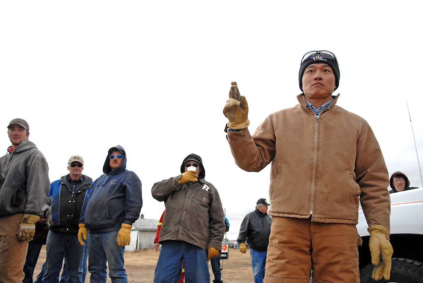 Sheldon Zou bids during an auction at a far, near Ogema, Saskatchewan, Canada. Zou immigrated from China to Ogema in 2008. Zou, his wife Linda and daughters Jennifer and Angela now own over 4,000 acres of land in the tiny community 115 kilometres south of Regina. MARK TAYLOR FOR THE GLOBE AND MAIL.