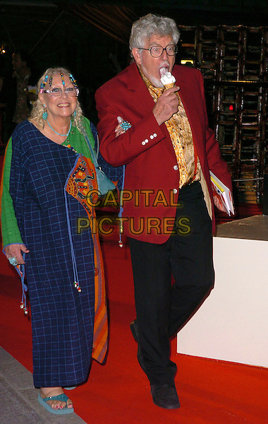 ROLF HARRIS & GUEST.The 2006 Summer Exhibition Preview Party at the Royal Academy in Piccadilly, London, UK..June 7th, 2006 .Ref: CAV.full length ice cream cone food eating blue checkered red suit jacket .www.capitalpictures.com.sales@capitalpictures.com.© Capital Pictures.