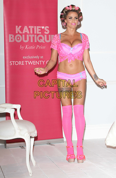 Katie Price (Jordan) .The launch photocall for Katie Price's new summer lingerie range for Store 21, The Worx, London, England..May 29th, 2012.full length pink lace top knotted bra cleavage belly stomach midriff knickers underwear tattoo tights stockings garter beige platform sandals shoes rollers curlers in hair hands arms.CAP/ROS.©Steve Ross/Capital Pictures.