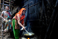 A woman prepares a meal on a fire outside her hut in the Mirpur slum in Dhaka.