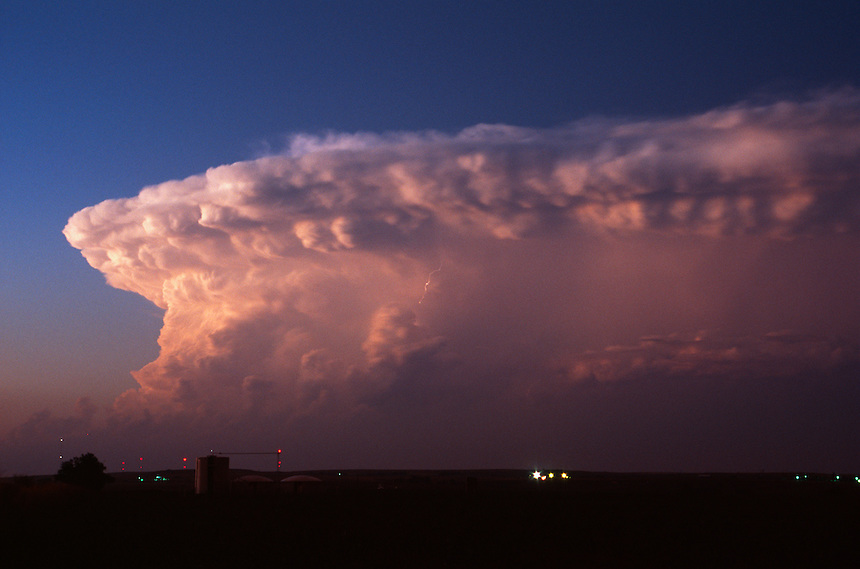 A cumulonimbus cloud is illuminated a pink color by the setting sun near Perryton Texas.