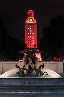 A vertical view of the UT Tower burnt orange for the graduating class of 2017 on the campus in downtown Austin.  In the forefront the Littlefield fountain was flowing with the burnt orange tower behind  with number 17 for the class of 2017.