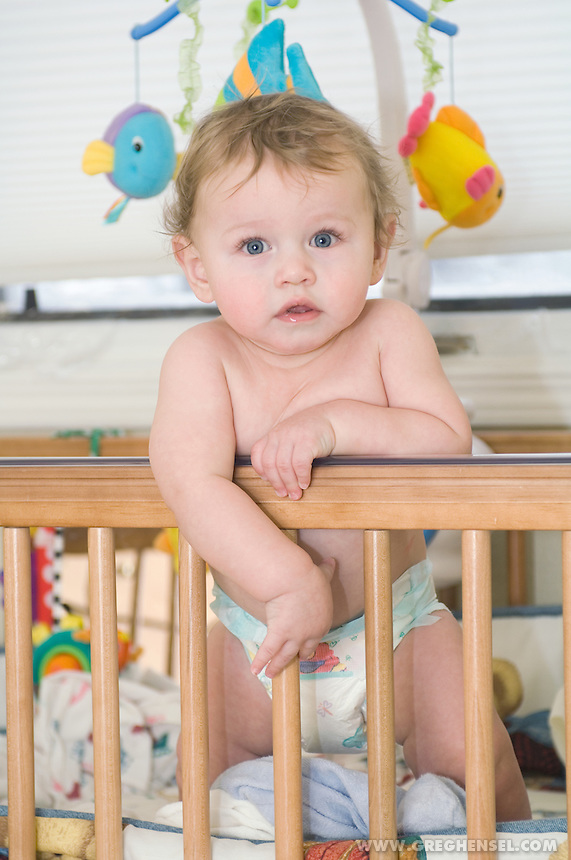 Baby boy in diapers leaning against the side of his crib.