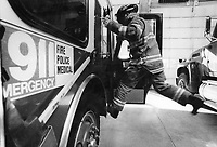 A fireman leaps into a fire truck during an emergency response.