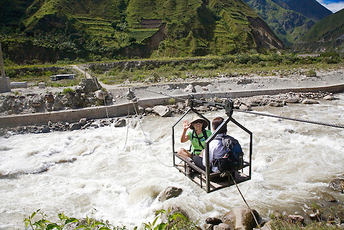 TWO TREKKERS CROSS THE URUBAMBA RIVER IN A BASKET IN PERU