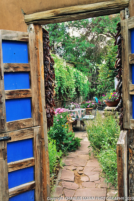 A colorful gate with blue trim opens to reveal a secret backyard garden nook in the home of Lupe Murcheson of Santa Fe.