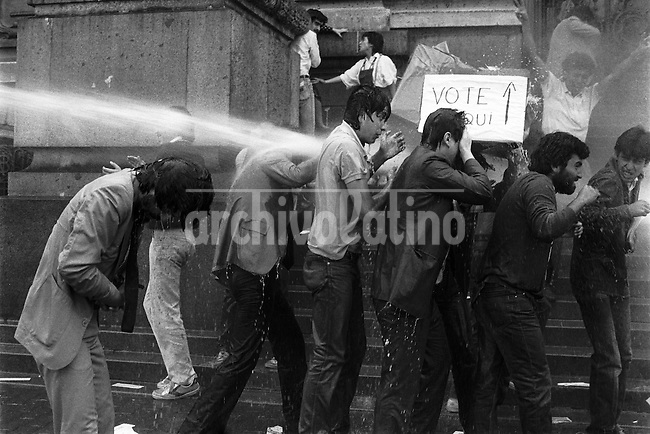 Marzo 1986 <br /> Opositores a la dictadura de Augusto Pinochet se congregan frente a la Biblioteca Nacional para exigir elecciones libres instalando simb&radic;&ge;licamente urnas de votaci&radic;&ge;n, los manifestantes  fueron reprimidos por la policia y varios de ellos detenidos.<br /> <br /> Forty years ago, on September 11, 1973, a military coup led by General Augusto Pinochet toppled the democratic socialist government of Chile. President Salvador Allende was killed during the  attack to seize  La Moneda presidential palace.  In the aftermath of the coup, a quarter of a million people were detained for their political beliefs, 3000 were killed or disappeared and many thousands were tortured.<br /> Some years later in 1981, while Pinochet ruled Chile with iron fist, a young photographer called Juan Carlos Caceres started to freelance in the streets of Santiago and the poblaciones or poor outskirts, showing the growing resistance against the dictatorship. For the next 10 years Caceres photographed every single protest and social movement fighting for the restoration of democracy. He knew that his camera was his only weapon, he knew that his fate was to register the daily violence and leave his images for the History.<br /> In this days Caceres is working to rescue and organize his collection of images in the project Imagenes de la Resistencia   . With support of some Chilean official institutions, thousands of negatives are digitalized and organized to set up the more complete visual heritage of this  violent period of Chile&acute;s history.