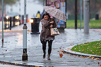 Monday  21 November 2014<br /> Pictured: A woman is battered by the rain and wind as she walks along with an umbrella<br /> Re: A yellow &quot;be aware&quot; weather warning has been issued as widespread heavy rain hits the country. The Met Office said gusts of winds could hit 50mph (80km/h) with localised flooding and disruption to travel.