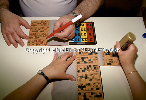 Bingo UK couple  playing Bingo, marking their cards as the numbers are called out. North London. 1990s 90s