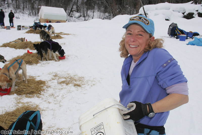Dee Dee Jonrowe feeds her dogs as the take a break on the Yukon river at the Eagle Island checkpoint.  2005 Iditarod Trail Sled Dog Race.