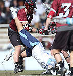14 February 2015: North Carolina's Luke Goldstock (in white) goes face first into the ground after a challenge from UMass's Kurt Hunziker (25). The University of North Carolina Tar Heels hosted the University of Massachusetts Minutemen in a 2015 NCAA Division I Men's Lacrosse match. UNC won the game 20-8.