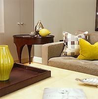 In the living room of a New York apartment an oversized leather ottoman holds a tray displaying a bright yellow ceramic vase