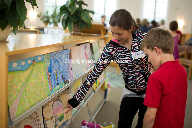 WINSTED, CT-2 June 2015-060215EC09-  Olivia Ficalora, 10, and her brother Anthony Ficalora, 7, check out some of the art work displayed during the fifth annual Peace Poster Competition at Northwestern Connecticut Community College in Winsted. Both children received prizes for their artwork, Olivia's poster is at the lar left. Children from ages five to eighteen received awards for the top three places Tuesday night. Erin Covey Republican-American
