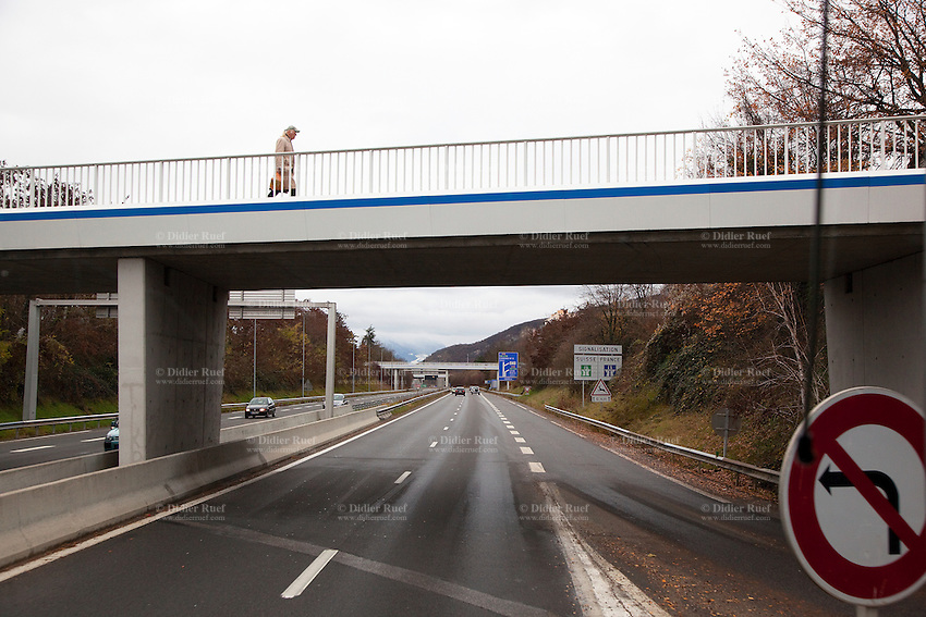 France. Haute-Savoie department. Gaillard. An old man walks alone on a bridge over the highway. 6.12.2011 © 2011 Didier Ruef