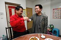 Li Fang (gauche) et Li Daquan (droite) boivent un verre de baijiu (« alcool de riz ») entre père et fils avant le repas du samedi soir. Li Fang est un grand amateur de baijiu, il entrepose même plusieurs caisses de crus différents dans la troisième chambre de l'appartement. Un ami lui en a envoyé un carton, et sinon, il préfère acheter les bouteilles à l'usine, « où c'est 30 RMB la bouteille, six fois moins cher qu'au supermarché », confie-t-il. Quant au putaojiu (« vin rouge »), il en a une bouteille, « pour goûter ». Photo par Lucas Schifres/Pictobank