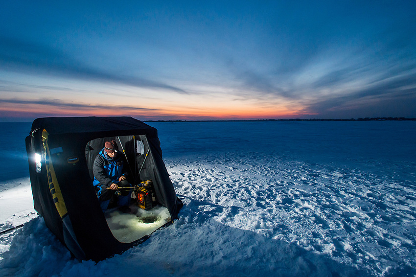 Ice fishing shelters illuminated from within at dusk on frozen Lake Michigan at Little Bay de Noc near Gladstone, Michigan.