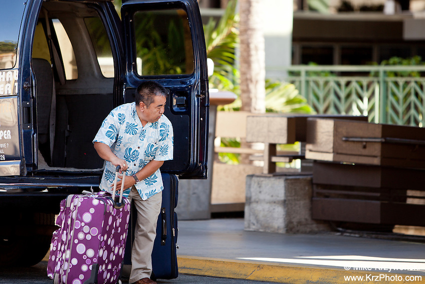 Local Asian male shuttle van driver unloading luggage at the Honolulu International Airport, O'ahu