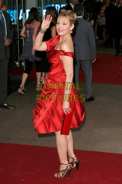 """KIM CATTRALL.Arrivals at the """"Sex And The City: The Movie"""" World Premiere, Odeon Leicester Square, London, England, UK. .May 12th 2008 .SATC full length off the shoulder red Vivienne Westwood dress cowel neck black strappy shoes sandals hand waving.CAP/AH.©Adam Houghton/Capital Pictures."""