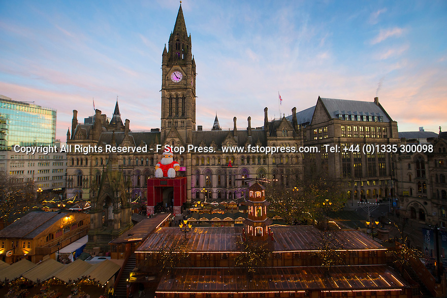 02/12/14<br /> <br /> As the sun sets, a giant Santa Claus overlooks the centrepiece of Manchester's Christmas market in Albert Square. The wooden buildings have all been built to accommodate the German style market which is spread over seven streets. <br /> <br /> ***ANY UK EDITORIAL PRINT USE WILL ATTRACT A MINIMUM FEE OF £130. THIS IS STRICTLY A MINIMUM. USUAL SPACE-RATES WILL APPLY TO IMAGES THAT WOULD NORMALLY ATTRACT A HIGHER FEE . PRICE FOR WEB USE WILL BE NEGOTIATED SEPARATELY***<br /> <br /> <br /> All Rights Reserved - F Stop Press. www.fstoppress.com. Tel: +44 (0)1335 300098