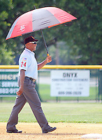 An umpire holds an umbrella to shield himself from the sun in the third inning of the Bordertown vs. Flemington American Legion state playoff Monday July 25, 2016 in Ewing, New Jersey.  (Photo by William Thomas Cain)