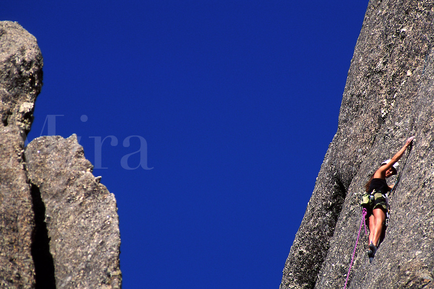 A rock climber ascends the nearly vertical side of a rock formation.
