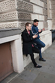 Two young men leaning on a wall check mobile phones in a London street