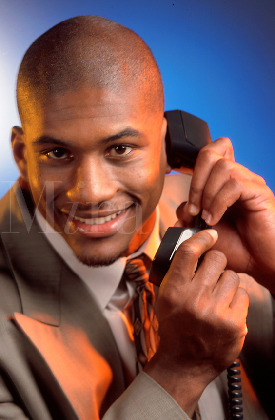 A smiling African American businessman talking on the telephone.