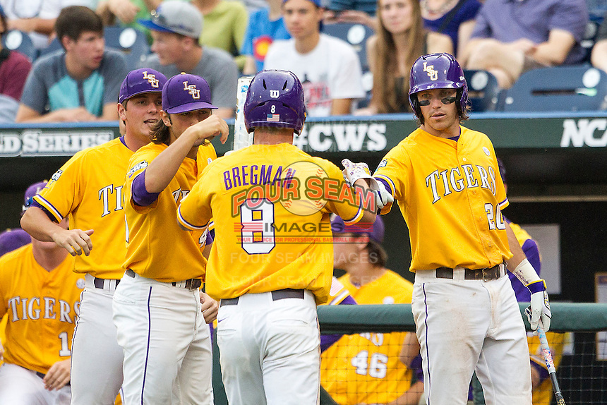 LSU Tigers third baseman Conner Hale (20) greets teammate Alex Bregman (8) after he scored against the TCU Horned Frogs in Game 10 of the NCAA College World Series on June 18, 2015 at TD Ameritrade Park in Omaha, Nebraska. TCU defeated the Tigers 8-4, eliminating LSU from the tournament. (Andrew Woolley/Four Seam Images)