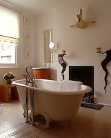 A freestanding bath in the centre of a contemporary bathroom with an open fireplace