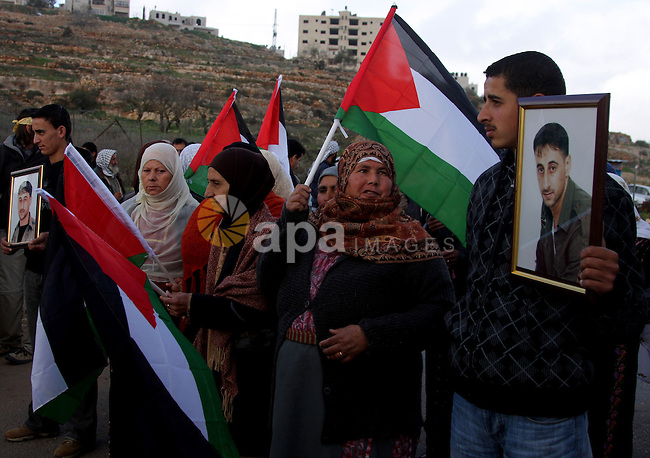 Palestinians hold flags outside Ofer prison near the West Bank city of Ramallah December 29, 2009, during a protest calling for the release of Palestinian prisoners from Israeli jails. Photo by Issam Rimawi