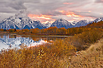 The sun underlights the clouds with pink and orange light during the sunset from Oxbow Bend in Grand Teton National Park.