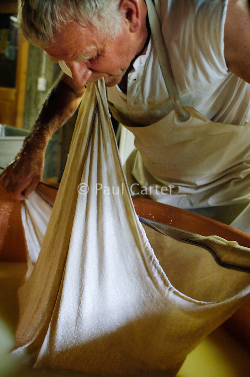Skimming the curds from the bottom of the cauldron using a large piece of cheese cloth and a length of sprung steel...Cowherd and cheesemaker spends 100 days in the summer, high up in the mountains, tending cows and pigs and making cheese at Balisalp and Käserstatt near Meiringen, Switzerland.
