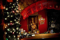The cashier at Castle Bar in Nanjing, China, sits behind her desk near a small Buddha statue and a Christmas tree.