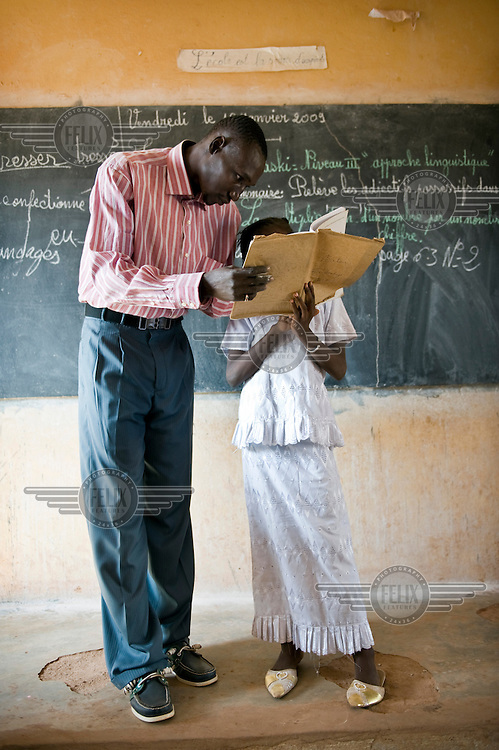 A girl works with her teacher at school in Bamako, supported by AAdec, one of the local partners of Oxfam Novib and Oxfam International.