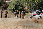 Israeli security forces gather at the area next to a road in the occupied southern West Bank at the entrance of the Israeli settlement of Kiryat Arba, on September 23, 2016, after a Palestinian was shot and wounded as he was attempting to stab Israelis at a bus stop, the army said. Photo by Wisam Hashlamoun