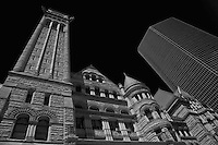 Looking up at the Old City Hall in Toronto in black and white with newer style glass office building in the background