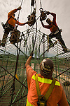 Construction workers rigging a rebar cage for transport.