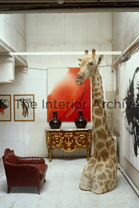The top half of a stuffed giraffe stands beside modern paintings and an ornate antique table in this living area