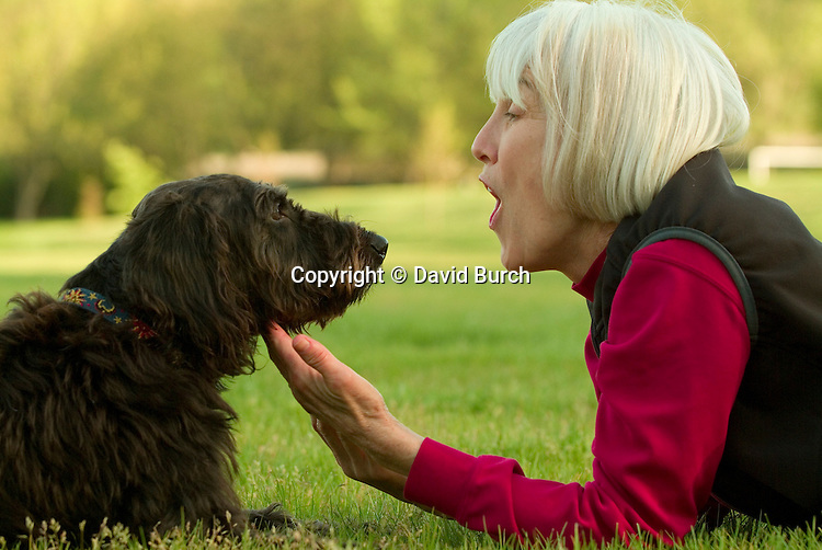 Mature woman playing with her pet dog, side view