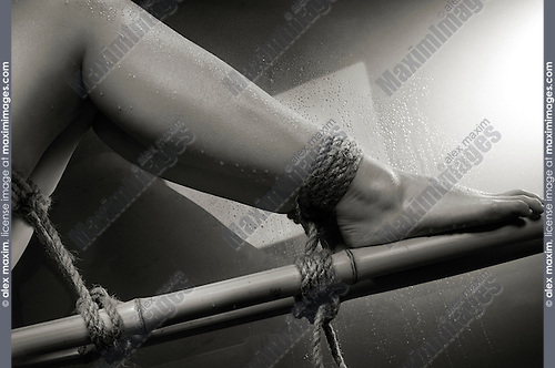 Closeup of wet woman legs tied with bondage rope to bamboo