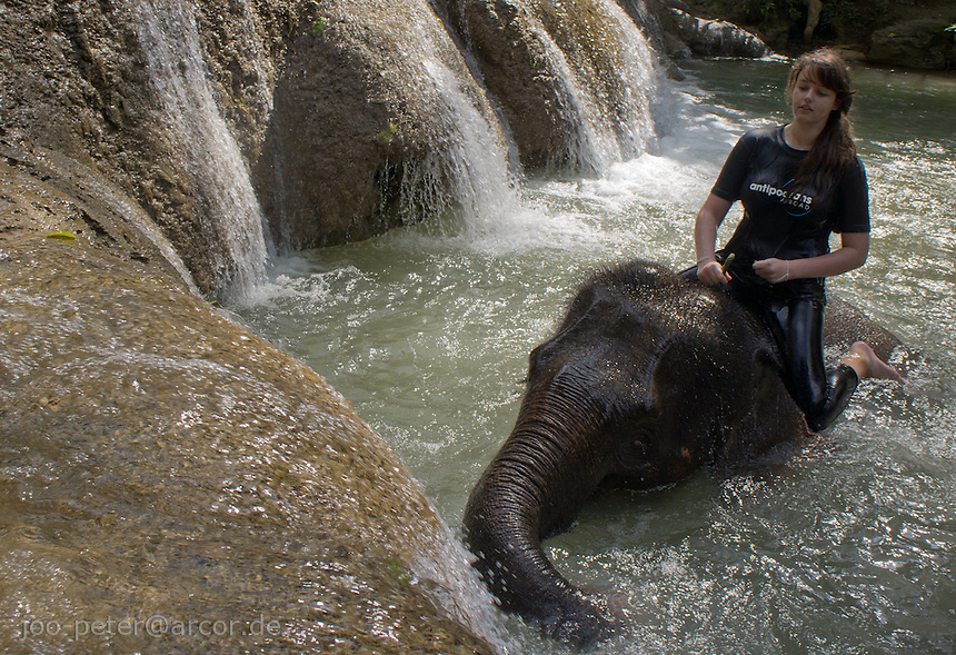 woman riding a elephant in waterfalls close to Luang Prabang,  Laos, 2012
