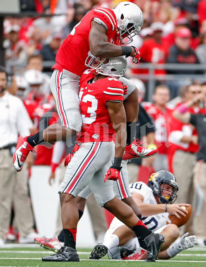 Ohio State Buckeyes linebacker Darron Lee (43) celebrates his sack of Kent State Golden Flashes quarterback Colin Reardon (10) with teammate Ohio State Buckeyes linebacker Curtis Grant (14) in the 2nd quarter of their game in Ohio Stadium on September 13, 2014.  (Dispatch photo by Kyle Robertson)