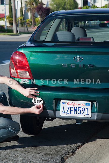 Man placing a 38 miles per gallon fuel efficiency bumper sticker installed on Toyota Echo car. Sticker from MPG Stickers (mpgstickers.com), a grassroots, nonprofit campaign which aims to accelerate the adoption of fuel efficient vehicles in the United States. California, USA. Property released from mpgstickers.com.