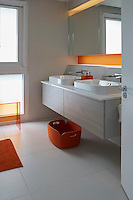 Small touches of bold, orange colour liven up an otherwise neutral bathroom.