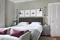 A set of black and white photographs hangs on the wall above the upholstered headboard in this bedroom, while a pair of black, movable wall lights is mounted above grey chests of drawers on either side of the bed