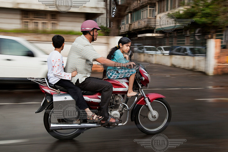 A man with his two children on a motorcycle.  For many Indians who cannot afford four-wheeled cars, a two-wheeled motorcycle is the only way to transport the family.