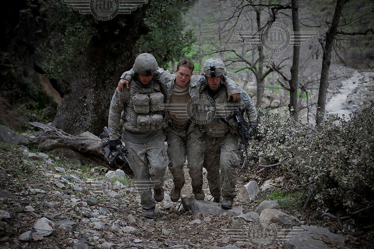 US Army Soldiers from Viper Company 126, 2nd Platoon, help medevac Specialist Tenut who collapsed suffering from exhaustion during a mission in the restive Korengal Valley, epicentre of the war and scene of fierce fighting with the Taliban.