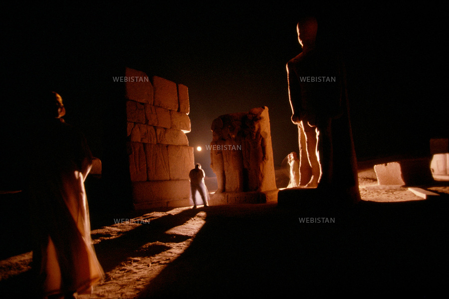 Egypt. Tanis. 1996. View by night of the monumental door of Amon's great temple in Tanis. Light effects on the tourists and statues silhouettes. Ramses II (baptised by the inhabitants, Hakamoun) is easily identifiable as well as the triad Horakhti-Re, Ramses and Ptah made of pink granite. These statues were patiently reconstituted from pieces found on the site. .Egypte. Tanis. 1996. Vue de nuit de la porte monumentale du Grand temple d'Amon a Tanis. Jeu de lumiere sur les silhouettes des touristes et celles des statues. On reconnait le colosse de Ramses II (baptise par les habitants Hakamoun) et au centre, faite de granit rose, la triade Horakhti-Re, Ramses et Ptah. Ces statues furent patiemment reconstituees a partir des morceaux retrouves sur le site.
