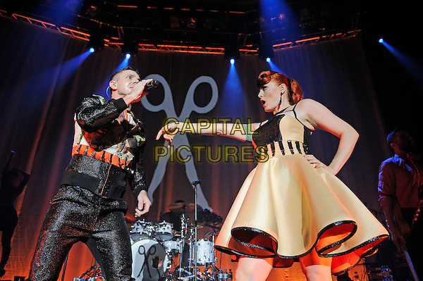 Jake Shears and Ana Matronic.Scissor Sisters performing live in concert, Camden Roundhouse, London, England. .23rd October 2012.on stage gig performance performing music half length black trousers orange green print jacket dancing yellow dress singing side profile hand on hip arm.CAP/MAR.© Martin Harris/Capital Pictures.